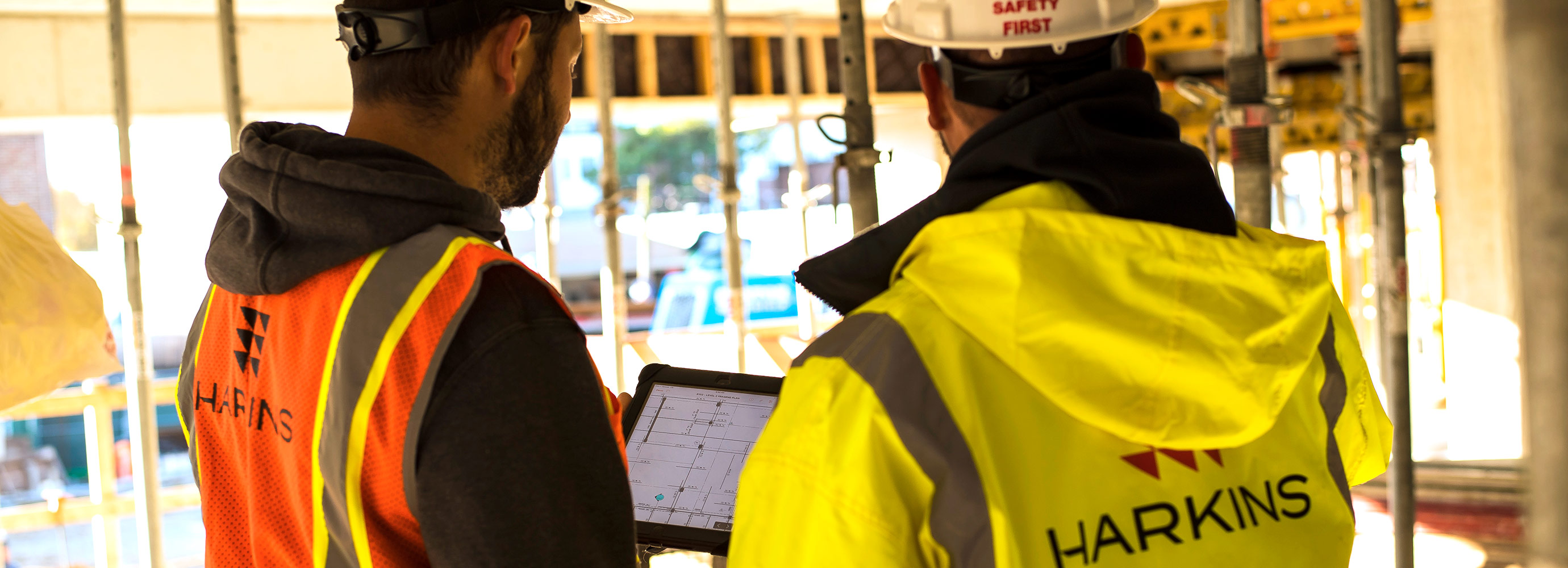 construction workers look over tablet of information
